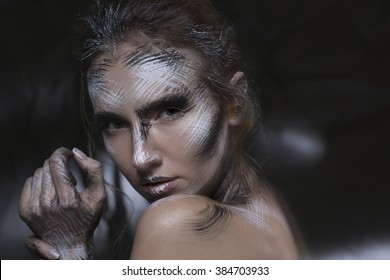 Artistic image of a beautiful blond girl with creative makeup. Hold neck. Mixed lightning techniques. High contrast