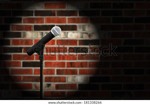 Artistic image of microphone against a rustic brick wall with spotlight effect and copy space.  Closeup with shallow dof.