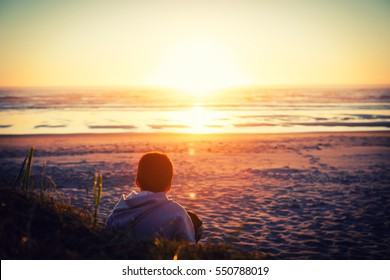 Artistic impression of a boy watching a sunset over the ocean, featuring an image from the back, intentionally blurring of scenery in the distance to create mood. Vintage Processing.