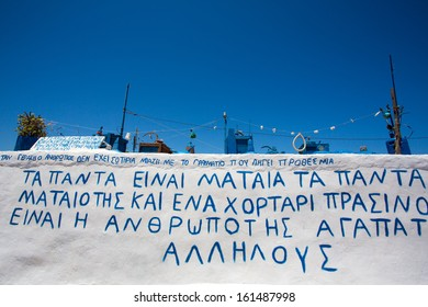 Artistic installation on a  roof of a house in Folegandros, the installation is made of strange objects all painted in blue, There is also a message about the crisis in Greece.