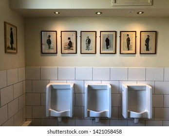 Artistic loo with portraits - Men's toilet of Lord Palrmeston, a pub in Tufnell Park serving British. North London, UK 08/07/2019. Three urinals along the wall.