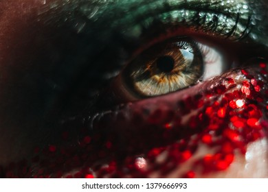 Artistic macro shoot of beautiful green eye with red glitter. Soft focus from vintage lens. Dragon concept.