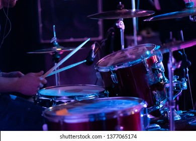 Artistic man playing on professional drum set on the stage