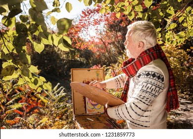 Artistic mind. Joyful artistic man thinking about his painting while mixing colors on the palette