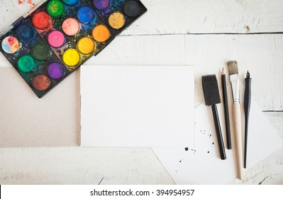 Artistic mockup with empty notebook and art supplies around including watercolor, brushes and calligraphy pens. Blank sketchbook on wooden desk.