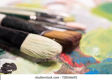Artistic Paint Brushes, close-up. Used artist brushes lying on the artist palette. Old oil artist brushes. Artistic artist art background. Copy space.