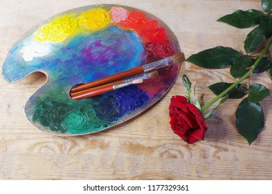 Artistic palete, paintbrushes and red rose