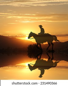 Artistic photography of a cowboy riding into the sunset with a mirror image of the horse and rider.