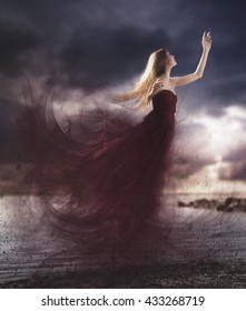 Artistic photography manipulation of a girl flying with a long red dress with a cloudy sky in the sunset. Blonde woman levitate.