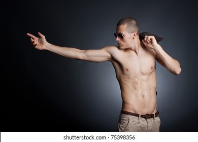 Artistic picture of a shirtless young male with sunglasses on a dark background