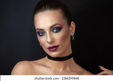 Artistic portet of a young girl on a dark background with blue glare of light on her face, radiant skin as well as bright and colorful makeup.