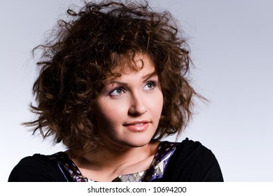 artistic portrait of a beautiful young woman with curly hair