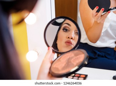 Artistic portrait cute young woman puckering lips while holding mirror