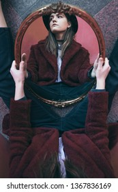artistic portrait with mirror reflection. between dream and reality. Red color stylish outfit. Hat and fur. Creative mood