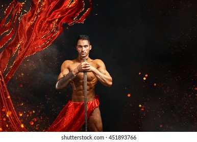 Artistic portrait of muscular male in red waving fabric with fire sparks holding sword.