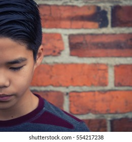 Artistic portrait of sad teenage Asian boy looking downward.  Intentionally cropped half of face for effect and to create open space for text.