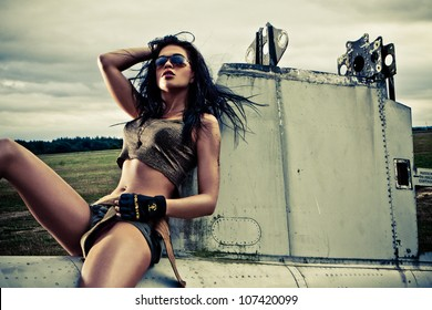 Artistic portrait of sexy slender long-legged woman in skimpy two piece outfit sitting on the fuselage of an abandoned old plane on a stortmy day