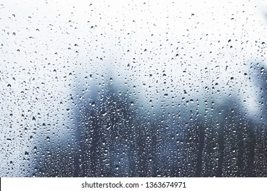 Artistic rain drops on the glass window as background. Blue color tone used.