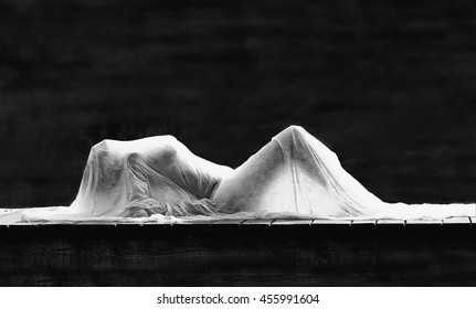 Artistic sensual Black and white photo of gorgeous sexy beautiful girl figure hiding in white material. Silhouette of woman body. Sensual female lying on stage. Woman in a shadow.  Woman secret