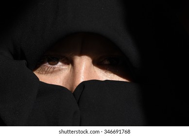 artistic shot of beautiful woman wearing black scarf hiding whole face
