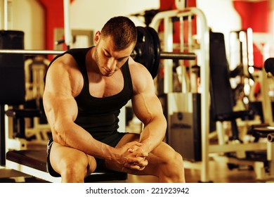 artistic shot, golden retouch, of a young bodybuilder hard training in the gym: resting on the bench press