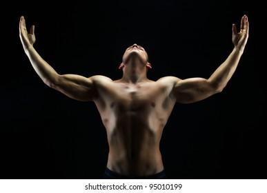 Artistic shot of a guy with his hands up against black background