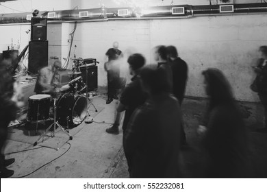 Artistic shot of underground concert with drummer and guitarists playing for concert goers with black and white film grain.