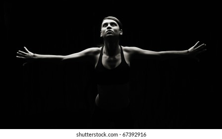 Artistic in studio, low key photo of slim attractive female in workout attire