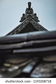 Artistic View of Temple Rooftop with Traditional Oni Goblin Face Decoration on Historic Buddhist Temple (Kurashiki, Japan).