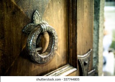 Artistic vintage dark edit of an old iron metal door knocker on an open wooden door, background with copy space for text