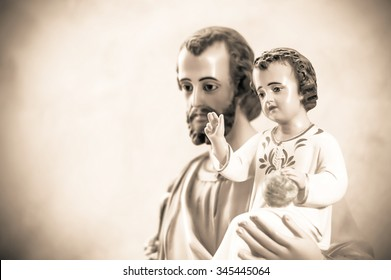 Artistic vintage sepia edit of a classical church statue of baby Jesus blessing, held by St Joseph. Artistic selective focus.