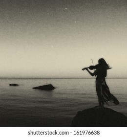 Artistic violine player at the sea. Art photo, noise is manually added