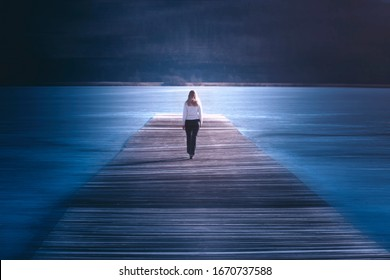 Artistic woman walking on wooden pier. Motion blur effect used.