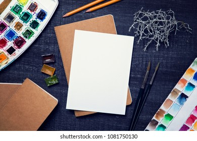 Artistic workplace mock up with watercolor paper and painting supplies