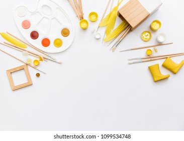 Artistic workspace with watercolor, paintbrush, palette, tools on white background. Flat lay, top view