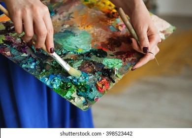 artists brushes and oil paints on wooden palette. macro artist's palette, texture mixed oil paints in different colors and saturation. palette with paintbrush and palette-knife hands.