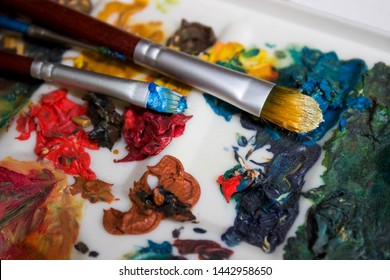 Artist's brushes and old palette with oil paints, drawing and creativity. Toned