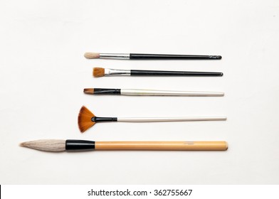 Artists brushes and pens displayed on isolated white background