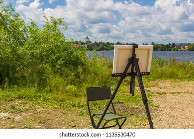 Artist's canvas on an easel in the background of the Russian landscape in summer.