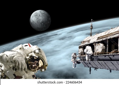 An artist's depiction of  a team of astronauts performing work on a space station while orbiting a large, alien planet as a large moon rises. Elements of this image furnished by NASA.