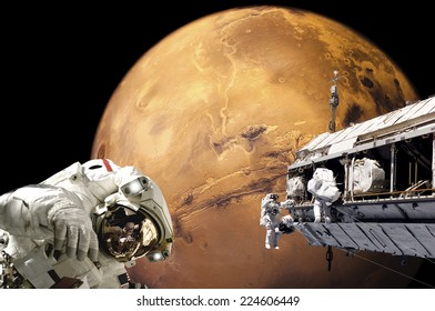 An artist's depiction of  a team of astronauts performing work on a space station while orbiting above the surface of Mars. Elements of this image furnished by NASA.