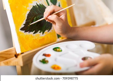Artist's hand with brush and palette painting a picture Sunflower