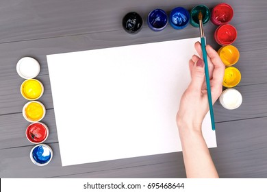 Artist's hand holds the brush over a blank sheet of white paper near open cans of colored paints on grey wooden board and ready to paint with watercolors.