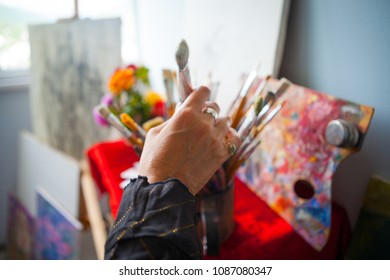 The artist's hand selects a brush from a large beam, against the background of the workshop.