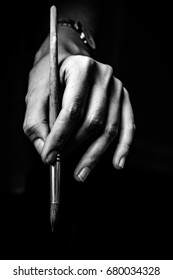 The artist's hands hold a brush. On a black background with deep shadows and bright highlights. Black and white conceptual image