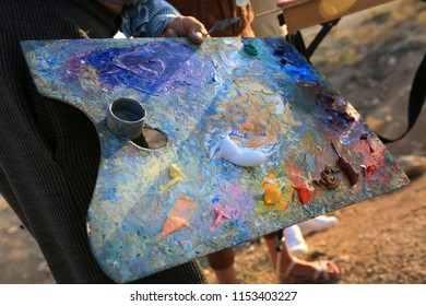The artist's hands hold a palette that draws oil painting outdoors