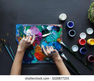 The artist's hands, paint palette brushes, different colors. The girl is drawing. The artist's tools for real art and inspiration. Dark light. Top View.