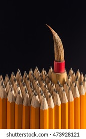 Artist's paint brush stands out from crowd of pencils n black background