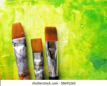 Artists paint brushes in studio in front of abstract background
