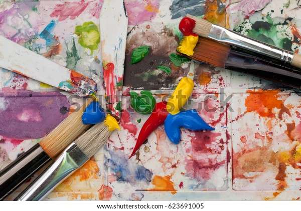 The artist's palette. Spray droplets, brushes and paint smears on a abstract background.